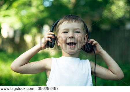 Funny little boy enjoying music in headphones outdoors.