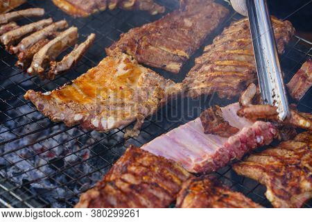 Grilled pork ribs on the grill or BBQ at street food market.