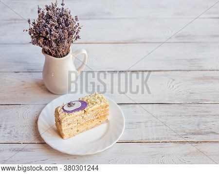 Lavender Cake On A White Plate On A White Wooden Background And A White Vase With Lavender Flowers.