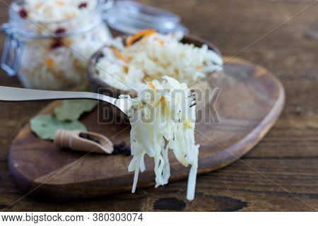Homemade Sauerkraut Or Barrel Cabbage On A Fork On A Rustic Wooden Background. In The Background Is