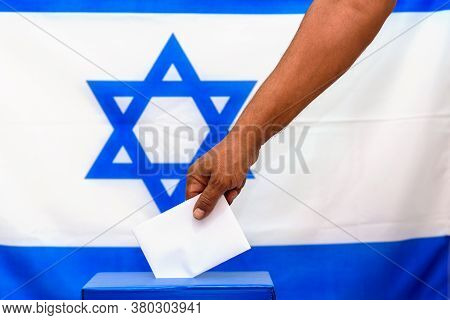 Israeli Man Putting A Ballot In A Ballot Box On Election Day. Close Up Of Hand With White Votes Pape