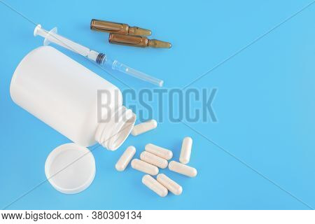 Pills, Capsules, Syringe, White Medical Containers Of Pills And Ampoules On Fabric Background. Medic