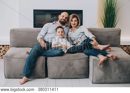 Caucasian Family Is Sitting On A Gray Sofa At Home Cuddling Up And Looking At The Camera. Father Hug