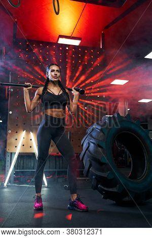Front View Of Muscular Woman In Sportswear Holding Sledgehammer On Shoulders Near Tire Wheel. Full L