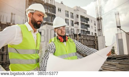 Professional Male Engineers In Workwear And Hardhats Examining Blueprint And Discussing Construction