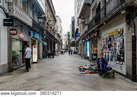 Corunna, Spain - July 20, 2020: View Of Migrant Street Vendors In Pedestrian Shopping Street In City
