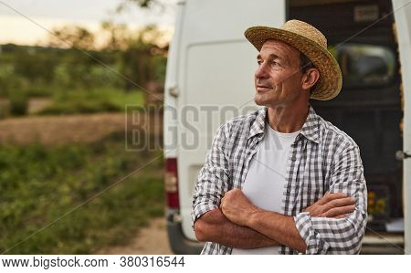 Positive Successful Middle Aged Male Farmer In Checkered Shirt And Straw Hat Looking Away While Stan