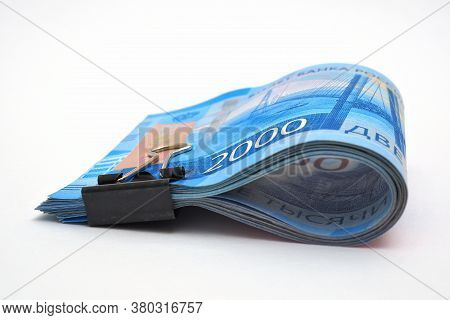 A Rolled Up Bundle Of Russian Bills Of 2000 Rubles. Money Tied With An Office Clip And Lie On A Whit
