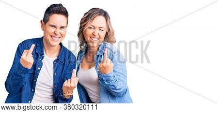 Couple of women wearing casual clothes showing middle finger doing  bad expression, provocation and rude attitude. screaming excited