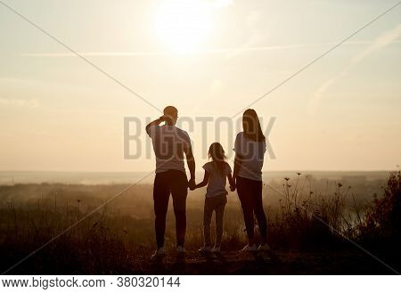 Silhouette Of A Family - Father, Mother And Daughter Standing On The Hill With Their Backs To The Ca