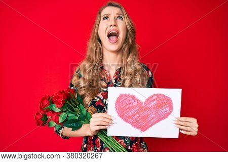 Young caucasian woman with blond hair holding heart draw angry and mad screaming frustrated and furious, shouting with anger looking up.