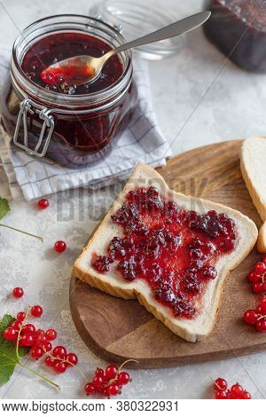 Top View Of A Sandwich With Homemade Jam Or Red Currant Jam On A Wooden Board And Next To A Jar Of J