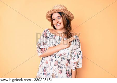 Young beautiful caucasian woman wearing summer dress and hat cheerful with a smile of face pointing with hand and finger up to the side with happy and natural expression on face