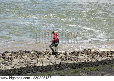 Terneuzen, The Netherlands, July 12, 2020, Sea Fisherman Is Standing On The Coast On The Turbulent S