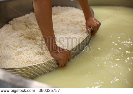 Worker Separating Curd From Whey In Tank At Cheese Factory, Closeup