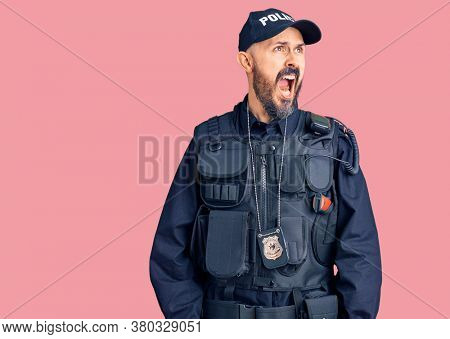 Young handsome man wearing police uniform angry and mad screaming frustrated and furious, shouting with anger. rage and aggressive concept.