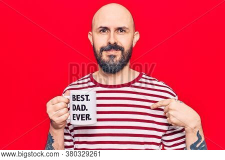 Young handsome man drinking mug of coffe with best dad ever message pointing finger to one self smiling happy and proud