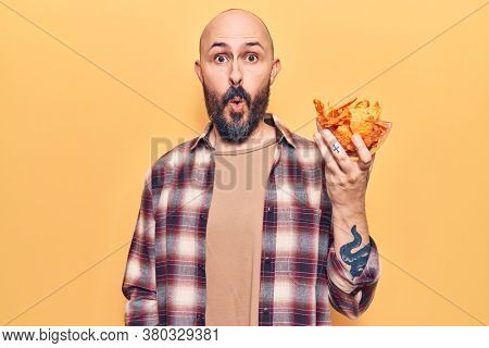 Young handsome man holding nachos potato chips scared and amazed with open mouth for surprise, disbelief face