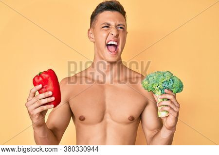 Young hispanic boy shirtless holding broccoli and red pepper angry and mad screaming frustrated and furious, shouting with anger. rage and aggressive concept.