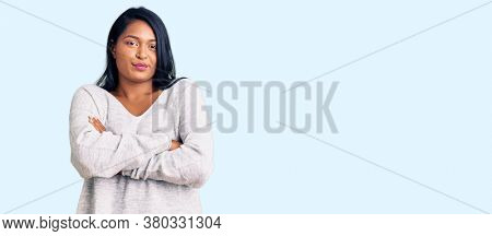 Hispanic woman with long hair wearing casual clothes skeptic and nervous, disapproving expression on face with crossed arms. negative person.