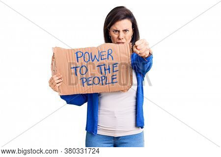 Young beautiful woman holding power to the people banner annoyed and frustrated shouting with anger, yelling crazy with anger and hand raised