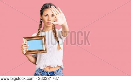 Beautiful caucasian woman with blonde hair holding empty frame with open hand doing stop sign with serious and confident expression, defense gesture
