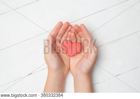 Human Hands Holding, Giving Heart Isolated On White Wooden Background. Concept Of Emotions, Feelings
