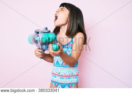 Young little girl with bang wearing swimsuit and watergun angry and mad screaming frustrated and furious, shouting with anger. rage and aggressive concept.