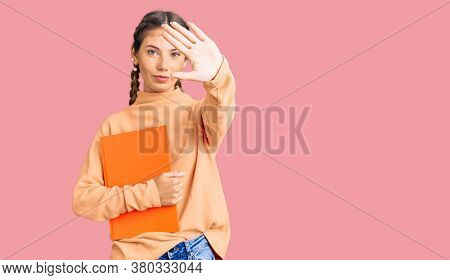 Beautiful caucasian woman with blonde hair holding book with open hand doing stop sign with serious and confident expression, defense gesture