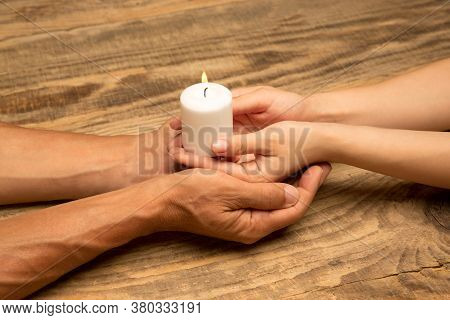 Hands Guarding, Holding A White Candle On Wooden Background With Copyspace. Home Warmth And Comfort,