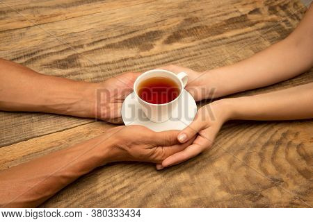 Hands Of Couple Holding Mug Of Tea, Top View On Wooden Background With Copyspace. Drinks, Home Comfo