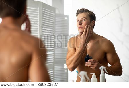 Charming Man Applying Lotion On His Face After Shaving, Looking In Mirror, Standing At The Bath Room