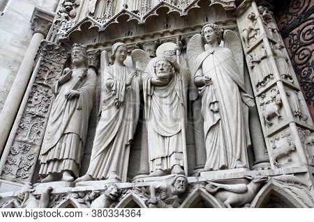 Saint Denis Holding His Head. Statue At The Left Portal Of Notre Dame De Paris. Decapitation. Portal