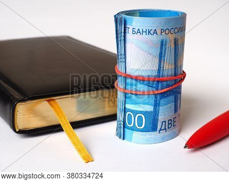 Black Diary, Red Pen And Bills Of 2000 Rubles. Banknotes Rolled Into A Tube And Tied With An Rubber