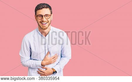 Handsome young man with bear wearing elegant business shirt and glasses smiling and laughing hard out loud because funny crazy joke with hands on body.