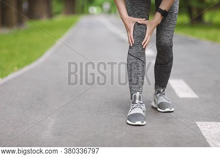 Knee Trauma. Unrecognizable Woman Jogger Hut Her Leg During Running Outdoors, Cropped Image With Fre