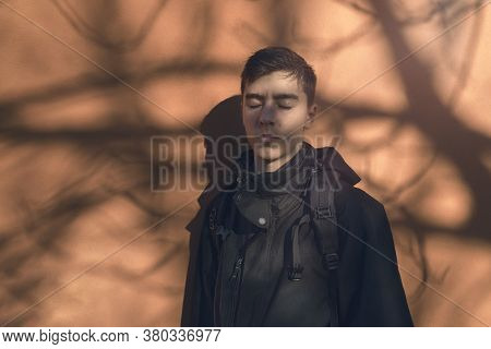 Portrait Of A Young Man Standing With His Eyes Closed In Front Of An Orange Wall With The Shadow Of
