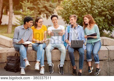 Highschool Students. Portrait Of Multiethnic Teens Studying In Park, Sitting On Border, Asian Boy Sh
