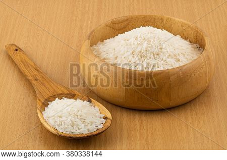 Jasmine Rice Filled In A Wooden Bowl And In A Wooden Spoon On Wooden Table