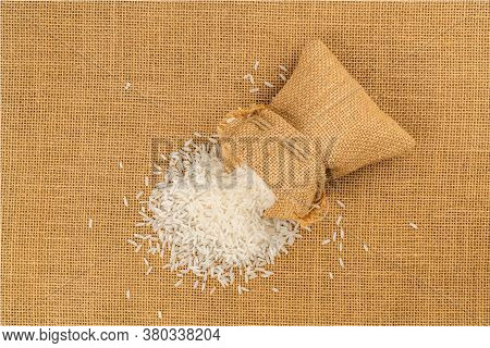 Top View Of Jasmine Rice Flow Out From A Sack On The Floor Covered With Sackcloth.