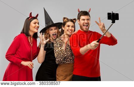 friendship, holiday and people concept - group of happy smiling friends in halloween costumes of witch, devil and cheetah taking picture by smartphone on selfie stick over grey background