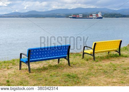 Blue And Yellow Benches On The Shore With A Cargo Ship On The Horizon