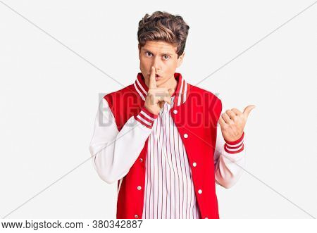 Young handsome man wearing baseball uniform asking to be quiet with finger on lips pointing with hand to the side. silence and secret concept.