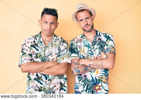 Young gay couple of two men wearing summer hat and hawaiian shirt skeptic and nervous, disapproving expression on face with crossed arms. negative person.