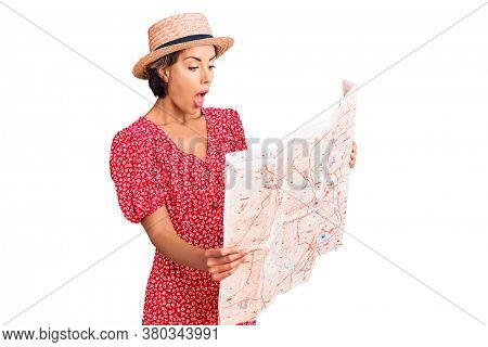 Young beautiful woman wearing summer hat holding map scared and amazed with open mouth for surprise, disbelief face
