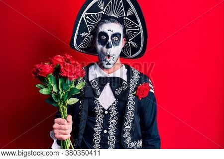 Young man wearing mexican day of the dead costume holding roses scared and amazed with open mouth for surprise, disbelief face