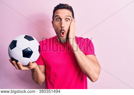 Young handsome player man playing soccer holding football ball over isolated pink background scared and amazed with open mouth for surprise, disbelief face