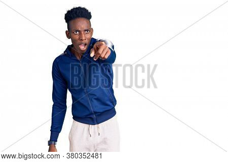 Young african american man wearing sportswear pointing with finger surprised ahead, open mouth amazed expression, something on the front