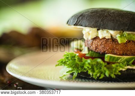 Vegan burger. Black bun, tofu-avocado salad, mayonnaise, cucumber, tomato, fresh salad. Delicious healthy hamburger food closeup served on a table for lunch in modern cuisine gourmet restaurant