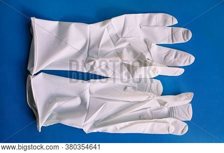 Pair Of Medical White Latex Protective Gloves On Blue Background. Protective Disposable Gloves Again